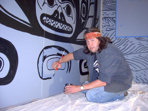 Tommy Joseph painting a shark graphic on the museum walls