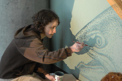 A student helping to projection paint salmon