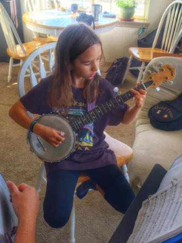 Learning banjo while wearing a Jamming Salmon shirt